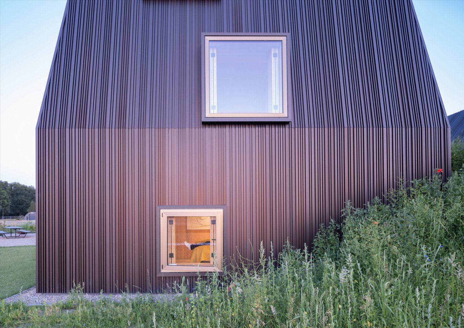 The Villa's construction and detailing also emulate the Dutch 'hoeve' or farmstead. The exterior dark bronze anodised aluminium cladding, chosen to seamlessly extend beyond the façade to the roof top, is p Ossip Architectuurfotografie
