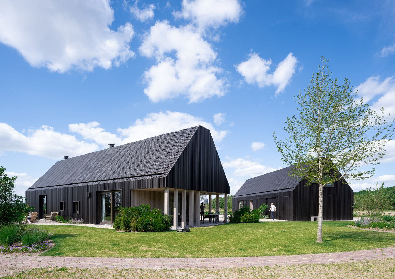 Of the two barns, one is furnished as a living room, kitchen with dining area and large veranda on the south-west side, with a workspace and playroom on the first floor. Ossip Architectuurfotografie