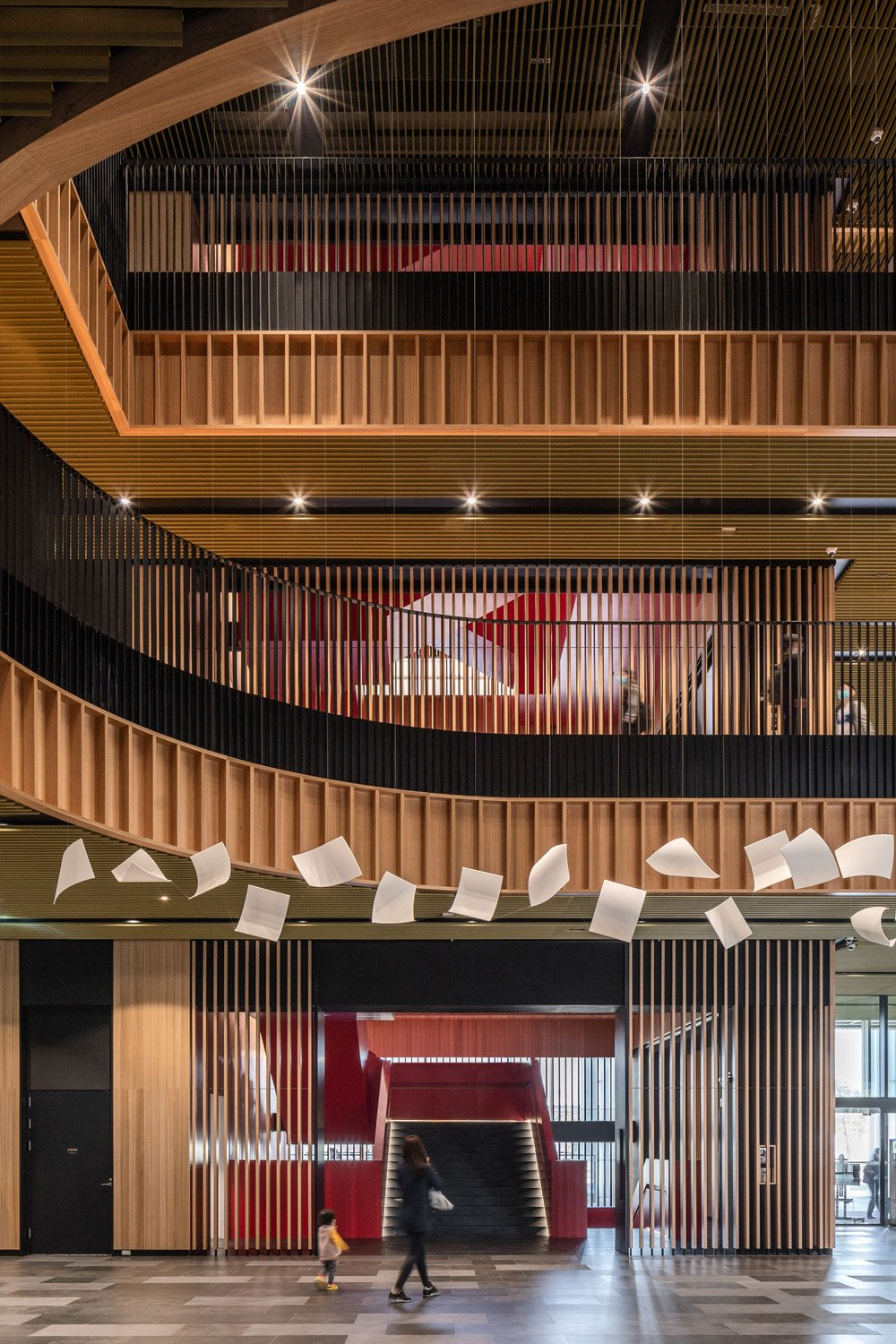 A sculptural staircase adds another playful element to the building, intersecting all levels and visible everywhere through the subtle wooden-slatted flight of stairs. Ethan Lee