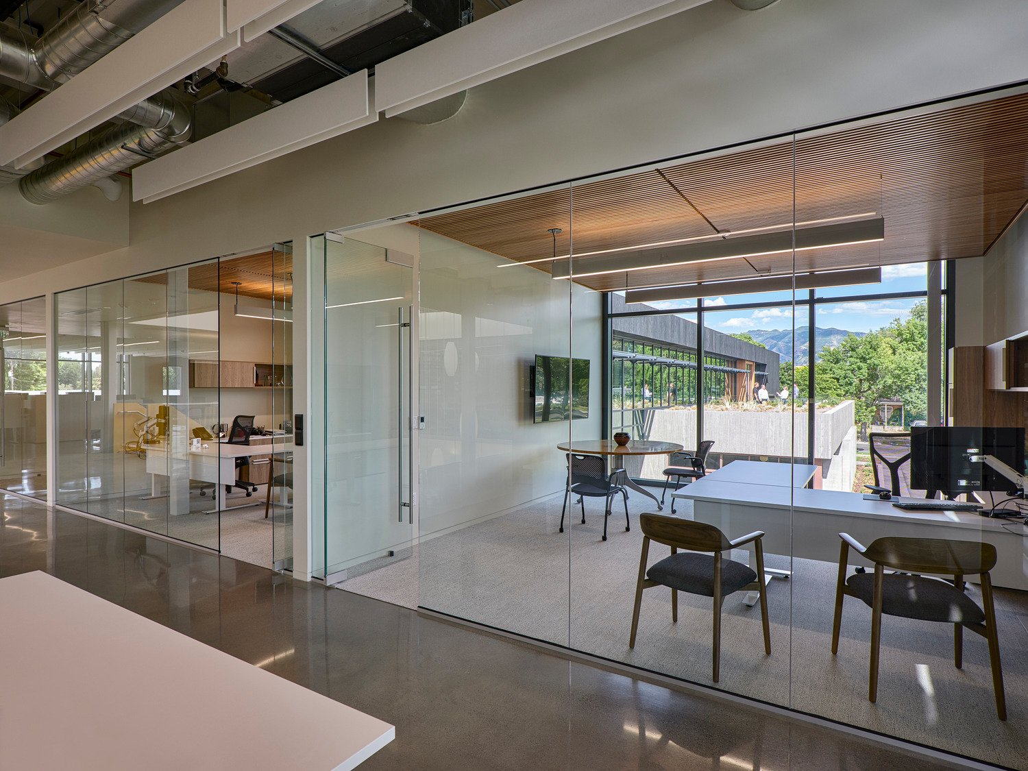A glass and louver system on the existing 2nd floor allow natural light to flow into executive suites and to bring levity to the building's volume. Tim Griffith
