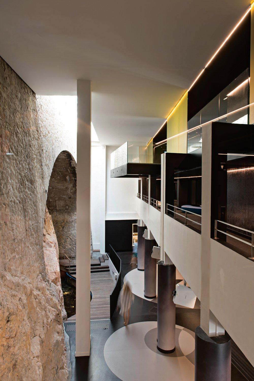 © Mads Mogensen, courtesy Teresa Sapey + Partners La parete in pietra delle antiche terme, lasciata a vista, fiancheggia la hall a doppia altezza.