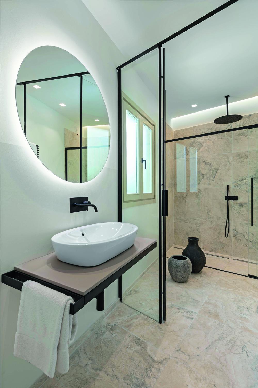 © Iuri Niccolai, courtesy Pierattelli Architetture Le pavimentazioni e i rivestimenti dei bagni in travertino con venature blu sono accostati al bianco di pareti e sanitari e al nero di rubinetterie e accessori