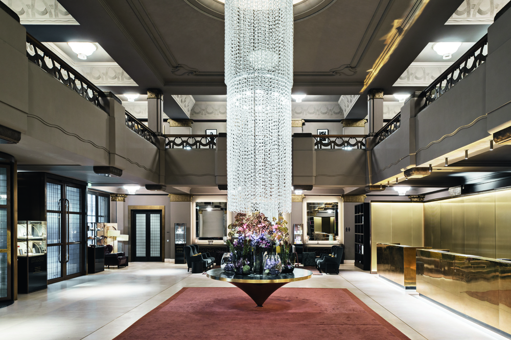 © Simone Bossi, courtesy Lissoni Casal Ribeiro A custom-made Murano glass chandelier hangs over a circular polished brass table in the middle of the double-height lobby.