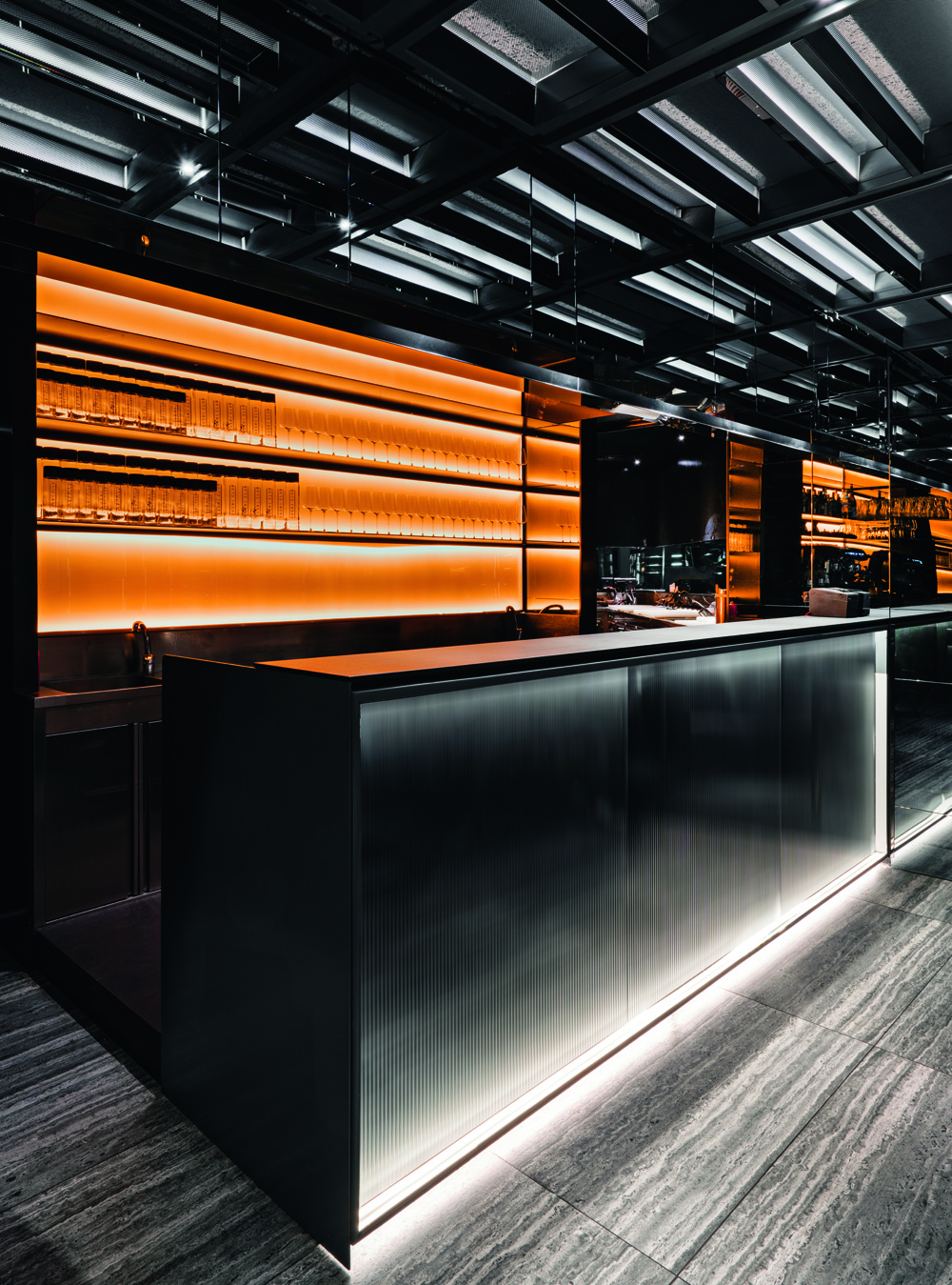 © Andrea Martiradonna, courtesy Maurizio Lai Architects The orange color of the wall behind the bar counter is reprised in the custom-made hanging lamps.