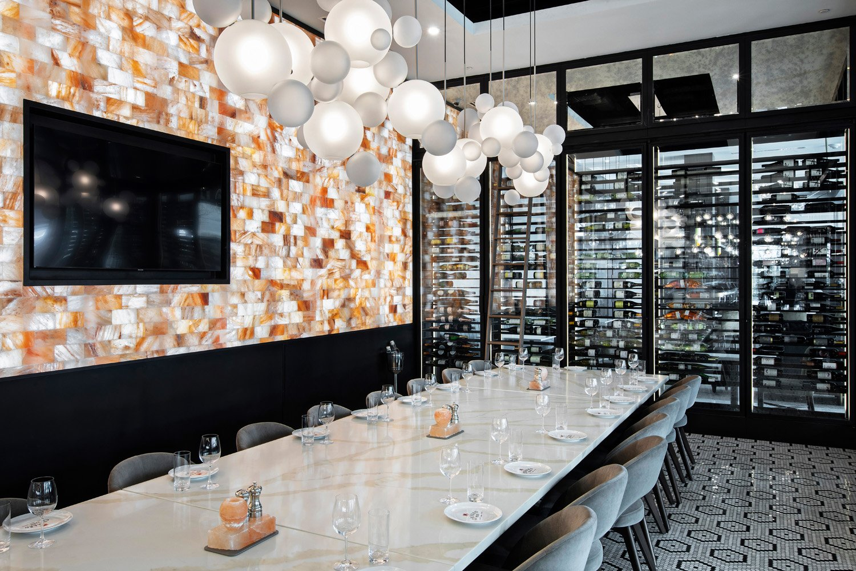 © DluxCreative, courtesy Lemay + Escobar Sul fondo della sala, in adiacenza alla parete in mattoncini  di sale rosa dell'Himalaya si trova un'area delimitata da pareti vetrate, di cui una costituita dalle vetrinette dove  sono riposte le bottiglie di vino.