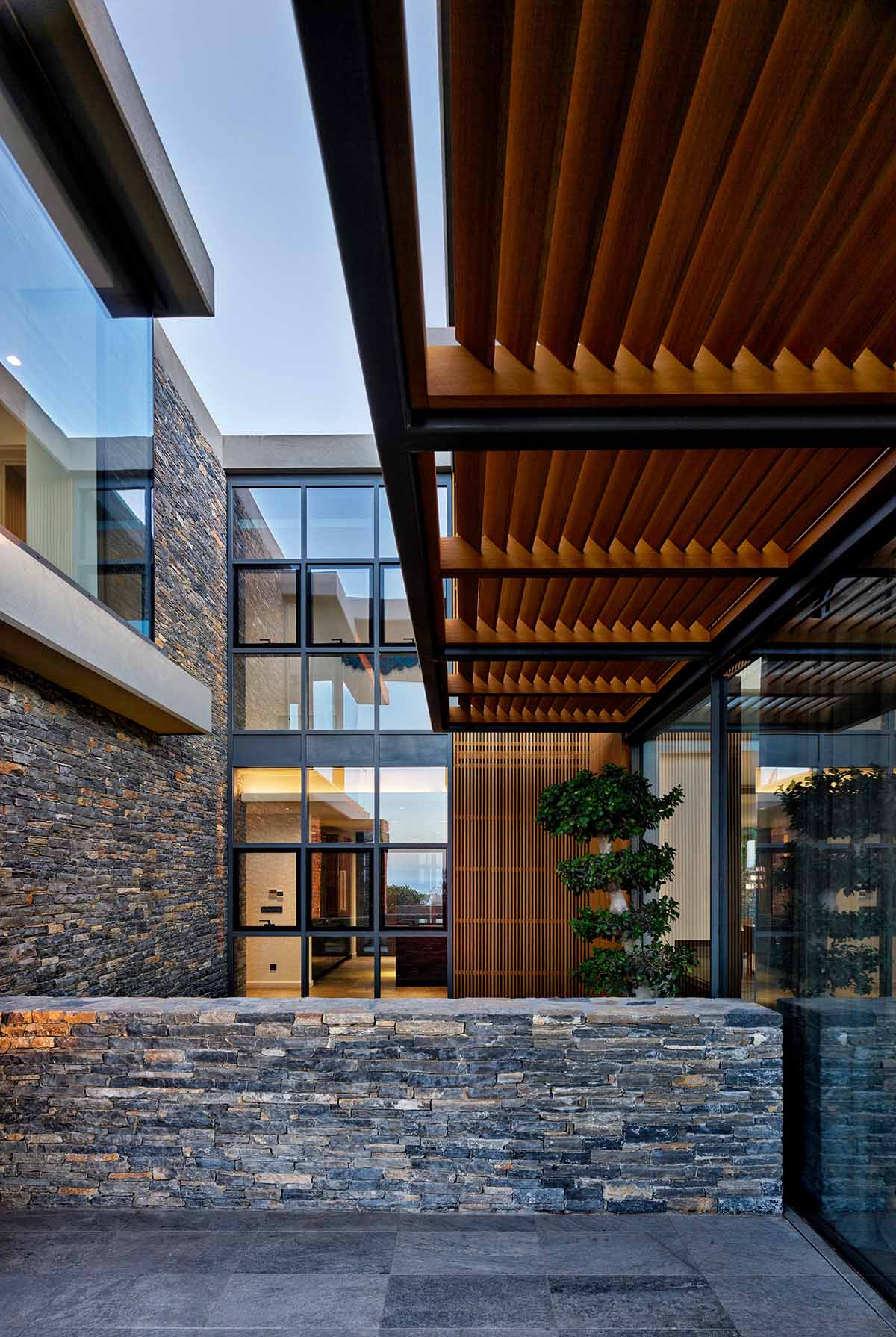 © Cemal Emden, courtesy EAA-Emre Arolat Architecture The design features a combination of stone, wood, glass and exposed concrete. The choice of materials and the way that the buildings' volumes fit into the hillside were conceived to create  a complex in harmony with the natural context.